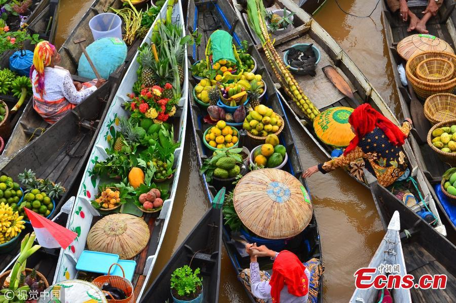 Hundreds of colorful boats tightly cram together at the Lok Baintan Floating Market to sell their hand-picked exotic fruit and vegetable in the Banjar district of Indonesia. The Lok Baintan floating market is in Southern Kalimantan Island dates back more than 500 years. Local people rely heavily on the waterways to make a living, with the markets now becoming tourist attractions.  (Photo/VCG)