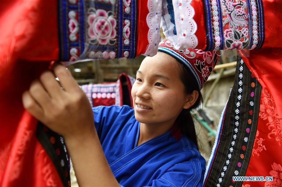 Yang Xinghe embroiders Miao costumes at Xinjiang Village in Taijiang County of Qiandongnan Miao and Dong Autonomous Prefecture, southwest China\'s Guizhou Province, on Nov. 4, 2018. Born with hearing loss, Yang Xinghe, 28, is a female of the Miao ethnic group, who are engaged in Miao embroidery at the village. She learned embroidery from her mother when she was only a child, and has been a locally well-known master now.(Xinhua/Liu Kaifu)