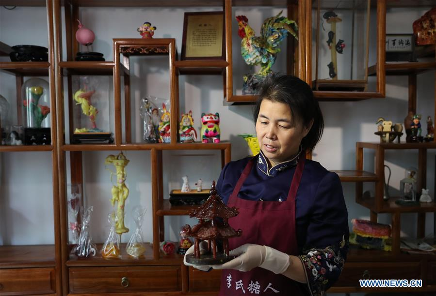 Folk artist Li Fengyan shows one of her sugar sculptures in Shenyang, northeast China\'s Liaoning Province, Nov. 6, 2018. The sugar sculpture of the Li family was listed as an intangible cultural heritage by the city of Shenyang. As the fifth-generation inheritor of her family\'s craft, Li Fengyan is making efforts to pass down the set of sugar-sculpting know-hows to her apprentices. (Xinhua/Yang Qing)