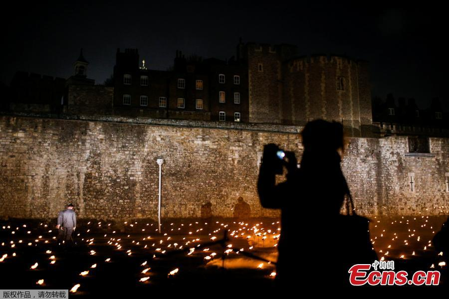 A woman photographs lit torches that are part of the installation \