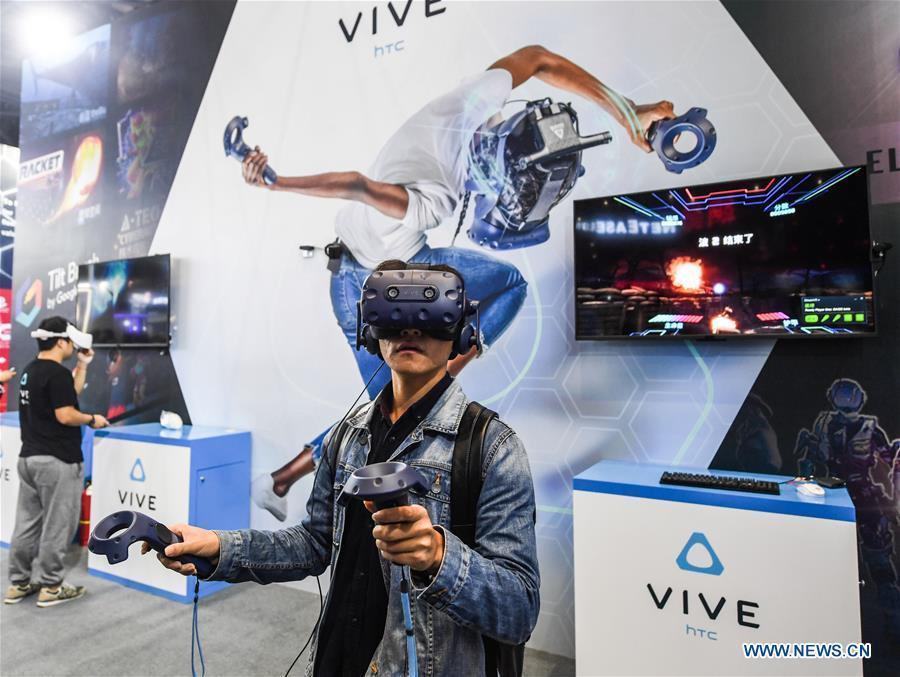 A visitor tries a virtual reality (VR) device at the Light of Internet Expo of the fifth World Internet Conference in Wuzhen Township of Tongxiang, east China\'s Zhejiang Province, Nov. 6, 2018. Opening here on Tuesday, the exposition focuses on the world\'s most recent internet development trends and cutting-edge technologies, showing the latest internet technologies, achievements, products and applications of more than 430 enterprises and institutions from home and abroad. (Xinhua/Xu Yu)