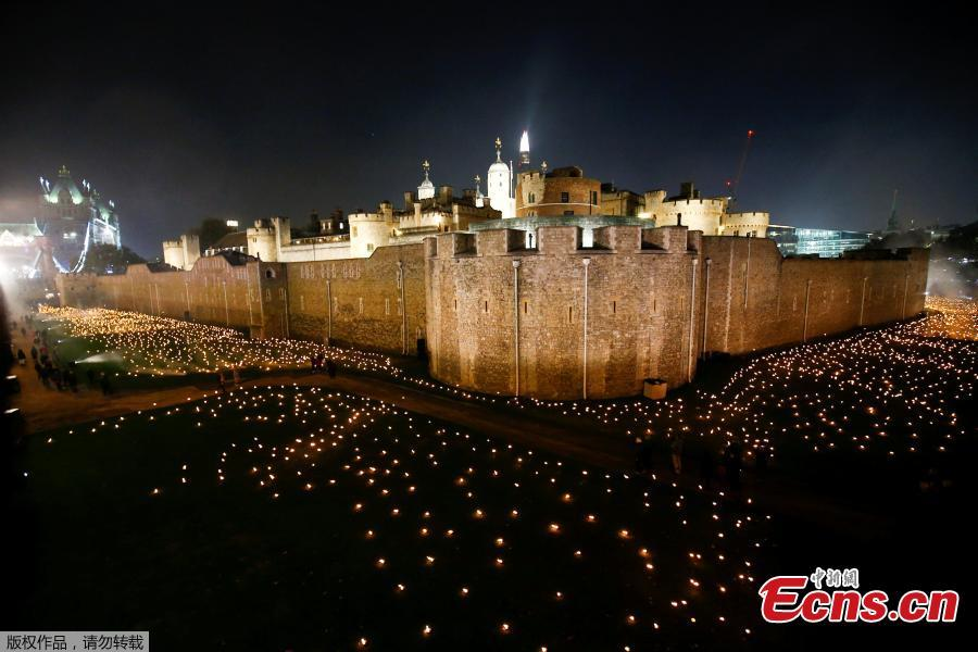 The moat of the Tower of London are seen filled with thousands of lit torches as part of the installation \