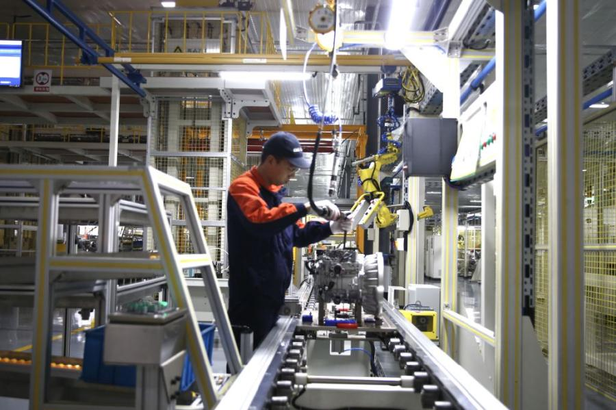 A technician operates a machine at the workshop of Jiaxing Xuanfu Automatic Transmission Co. (Photo/China Daily)
