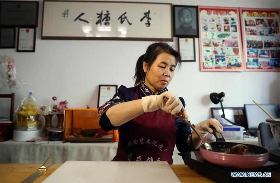 Folk artist Li Fengyan prepares syrup to make sugar sculptures in Shenyang, northeast China\'s Liaoning Province, Nov. 6, 2018. The sugar sculpture of the Li family was listed as an intangible cultural heritage by the city of Shenyang. As the fifth-generation inheritor of her family\'s craft, Li Fengyan is making efforts to pass down the set of sugar-sculpting know-hows to her apprentices. (Xinhua/Yang Qing)