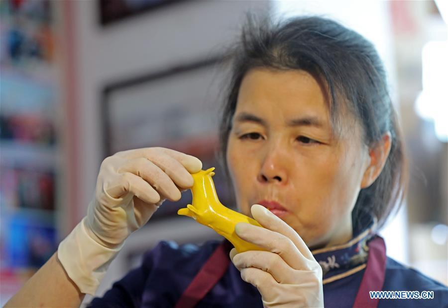 Folk artist Li Fengyan works on a sugar sculpture in Shenyang, northeast China\'s Liaoning Province, Nov. 6, 2018. The sugar sculpture of the Li family was listed as an intangible cultural heritage by the city of Shenyang. As the fifth-generation inheritor of her family\'s craft, Li Fengyan is making efforts to pass down the set of sugar-sculpting know-hows to her apprentices. (Xinhua/Yang Qing)