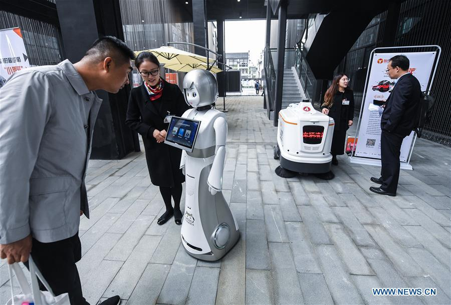 A visitor (L) interacts with a robot at the Light of Internet Expo of the fifth World Internet Conference in Wuzhen Township of Tongxiang, east China\'s Zhejiang Province, Nov. 6, 2018. Opening here on Tuesday, the exposition focuses on the world\'s most recent internet development trends and cutting-edge technologies, showing the latest internet technologies, achievements, products and applications of more than 430 enterprises and institutions from home and abroad. (Xinhua/Xu Yu)