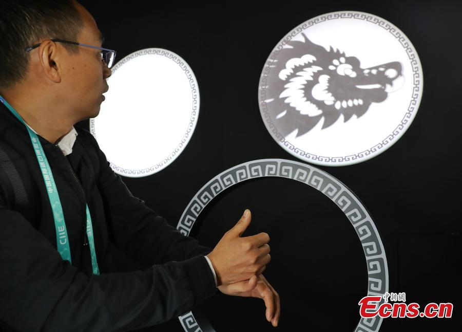 Using TensorFlow, an open source machine learning platform, Google's ShadowPlay enables visitors to transform shadow figures from hand gestures into digital animations at the first China International Import Expo (CIIE) in Shanghai, east China, Nov. 7 2018. The installation, built using TensorFlow, uses AI to recognize a person's hand gestures and then magically transform the shadow figure into digital animations representing the 12 animals of the Chinese zodiac and in an interactive show. (Photo: China News Service/Zhang Hengwei)