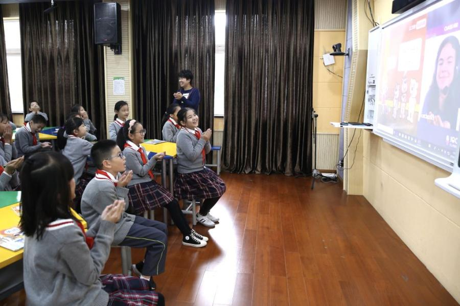Students from Wuzhen Zhicai Primary School interact with a foreign teacher in Canada on a video call during an English class. (Photo/China Daily)