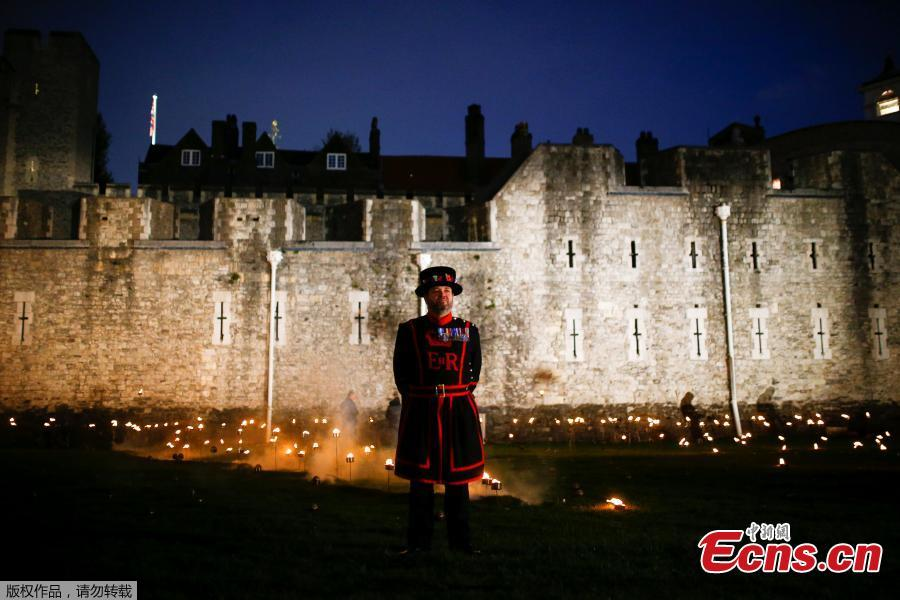 A Yeoman of the Guard stands amongst lit torches that are part of the installation \
