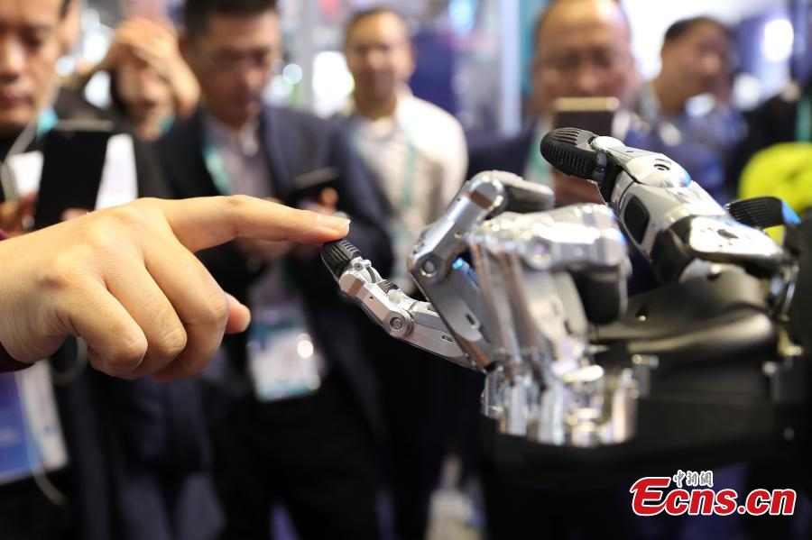 Visitors are attracted by a robotic hand shown at the first China International Import Expo (CIIE) in Shanghai, east China, Nov. 7 2018. The SCHUNK SVH 5-finger gripping hand is amazingly similar to the human model in terms of size, shape and agility. Nine drives enable the robotic hand to carry out gripping operations like holding a needle. (Photo: China News Service/Zhang Hengwei)