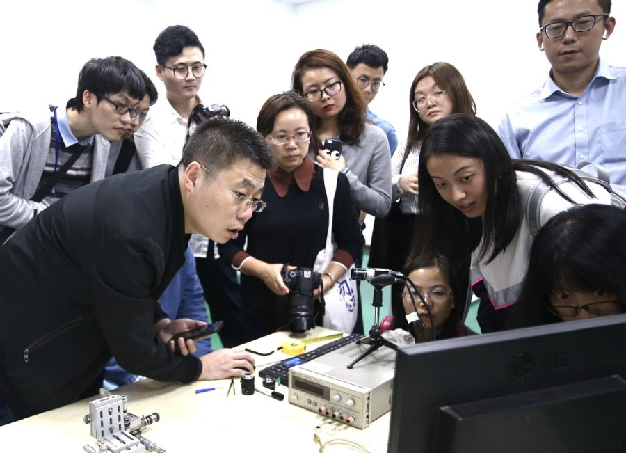 Yin Xiaodong (left), CEO of Jiaxing Yuguang Optoelectronic Technology Co, shows visitors how the Face ID feature of an iPhone X works with the help of an infrared camera at the company\'s office in Tongxiang Science and Technology Entrepreneurs Park, in Tongxiang, Zhejiang Province. [(Photo/China Daily)
