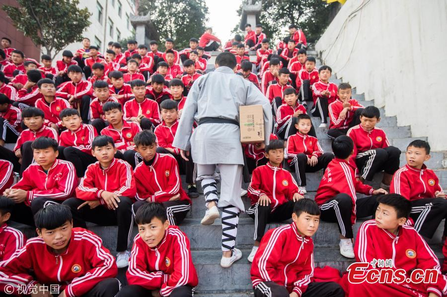 Wearing monk\'s robes, two Kung fu masters do a part time job as delivery man in Dengfeng city, Central China's Henan province. With their special stunts of martial arts, the two can give a hand to local couriers in preparation for the approaching annual Singles Day online shopping extravaganza on November 11. (Photo/VCG)