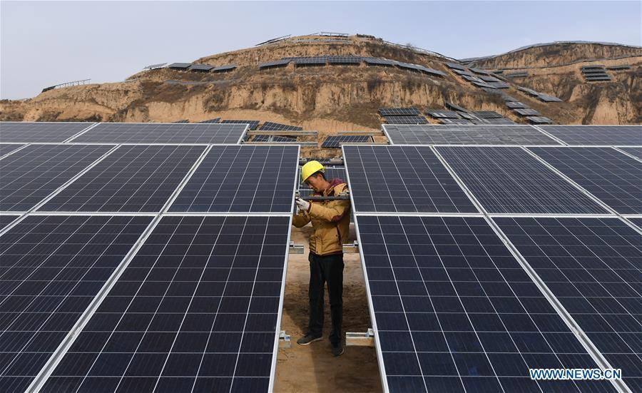 A worker checks solar panels at a photovoltaic power station built under an inter-village poverty relief program in Huojiaping Village of Yihe Township, Suide County, northwest China\'s Shaanxi Province, Nov. 7, 2018. Located on the Loess Plateau, Suide County has abundant sunshine and idle lands which are ideal for the construction of photovoltaic power stations. Currently, local authorities are working with a provincial branch of electricity service provider State Grid on a 33-megawatt photovoltaic power station. (Xinhua/Liu Xiao)