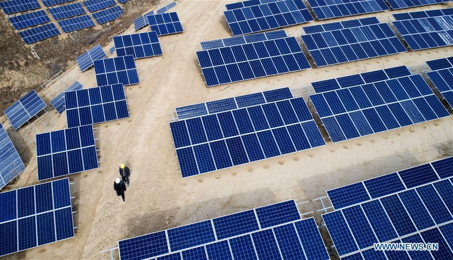 In this aerial photo taken on Nov. 7, 2018, workers patrol a photovoltaic power station built under an inter-village poverty relief program in Huojiaping Village of Yihe Township, Suide County, northwest China\'s Shaanxi Province, Nov. 7, 2018. Located on the Loess Plateau, Suide County has abundant sunshine and idle lands which are ideal for the construction of photovoltaic power stations. Currently, local authorities are working with a provincial branch of electricity service provider State Grid on a 33-megawatt photovoltaic power station. (Xinhua/Liu Xiao)
