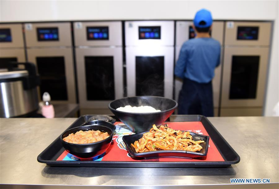 A worker operates a cooking machine in a cookless restaurant in central Beijing, capital of China, Nov. 7, 2018. The restaurant, equipped with 7 cooking machines that are programmed to prepare some popular Chinese dishes in minutes without human interference. Working along with smart payment and raw material supply systems, the cooking machine provides instant and standardized dishes. (Xinhua/Luo Xiaoguang)