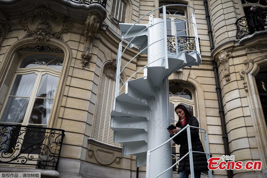 A woman stands on a section of stairs from the Eiffel Tower original structure displayed outside the Artcurial French auction house ahead of its forthcoming sale in Paris on November 8, 2018. (Photo /Agencies)