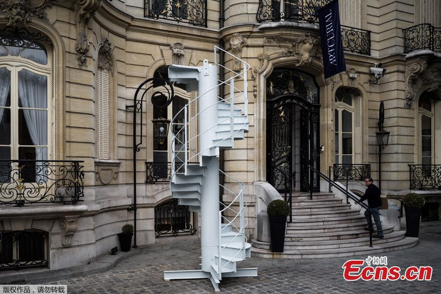 A man looks at section of stairs from the Eiffel Tower?s original structure displayed outside the Artcurial French auction house ahead of its forthcoming sale in Paris on November 8, 2018. (Photo /Agencies)