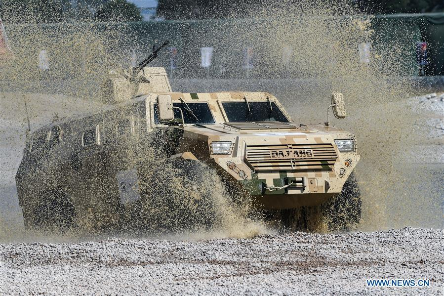 An armored vehicle wades through a puddle during a dynamic display of ground military equipments at the 12th China International Aviation and Aerospace Exhibition (Airshow China) in Zhuhai, south China\'s Guangdong Province, on Nov. 7, 2018. (Xinhua/Yang Guang)