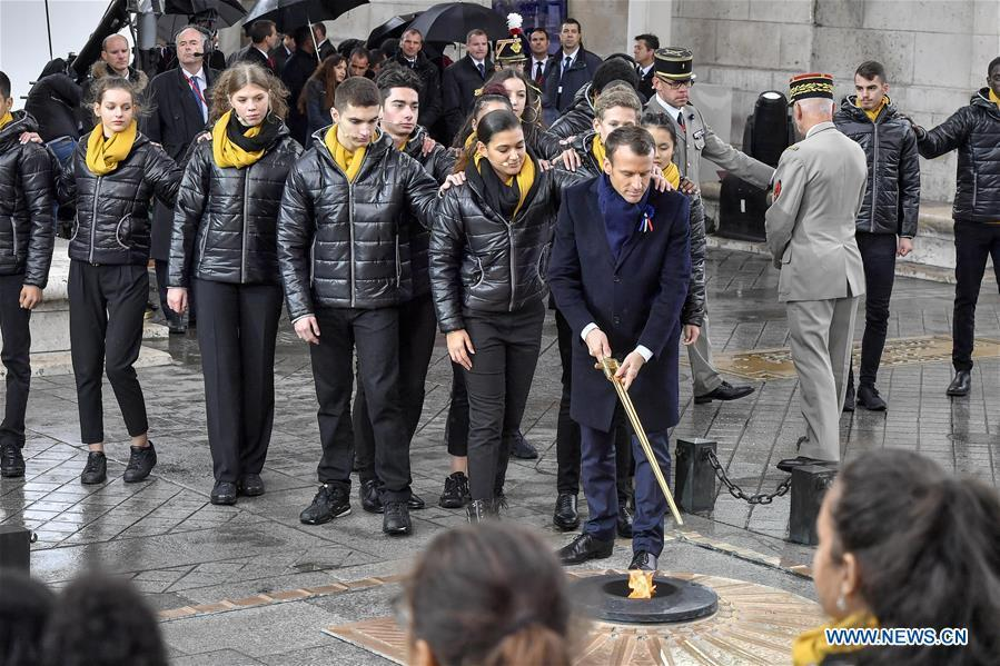 French President Emmanuel Macron revives a fire near the Tomb of the Unknown Soldier during a ceremony to mark the centenary of the Armistice of the First World War in Paris, France, Nov. 11, 2018. (Xinhua/Chen Yichen)
