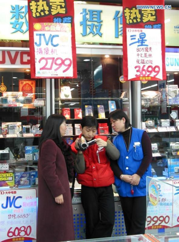 File photo taken on Nov. 27, 2003 shows staff members helping a customer adjust digital camera at an electric device shop in Beijing, capital of China. (Xinhua/Pang Xinglei)