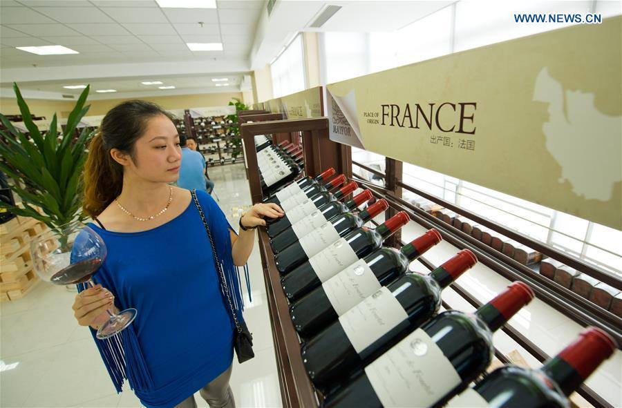 A woman looks at red wine imported from France at the first Chongqing international red wine cultural festival in Chongqing, southwest China, Sept. 2, 2012. (Xinhua/Liu Chan)