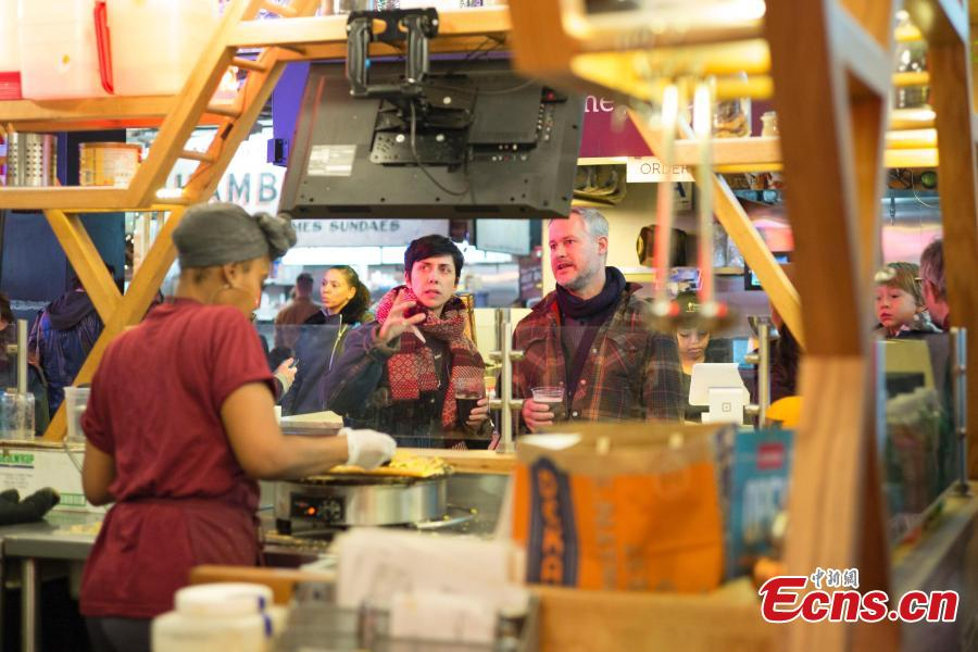 Customers wait for thier Jianbing, or the Chinese crepe at a kiosk in a food court in Brooklyn, New York, the United States on November 10, 2018. The Chinese snack ranges in cost from $13 to $15. (Photo: China News Service/ Liao Pan)