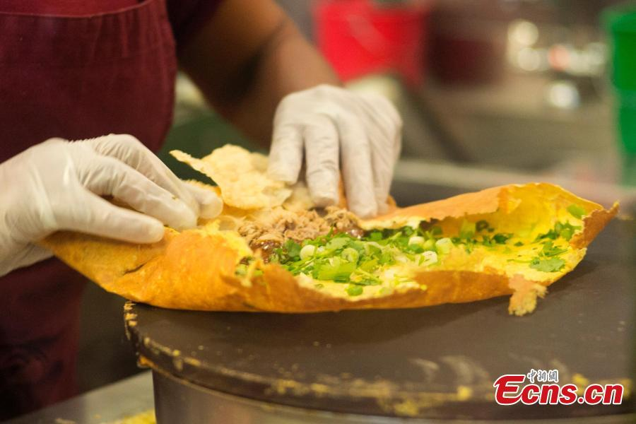 A worker makes Jianbing, or the Chinese crepe at a kiosk in a food court in Brooklyn, New York, the United States on November 10, 2018. The Chinese snack ranges in cost from $13 to $15. (Photo: China News Service/ Liao Pan)