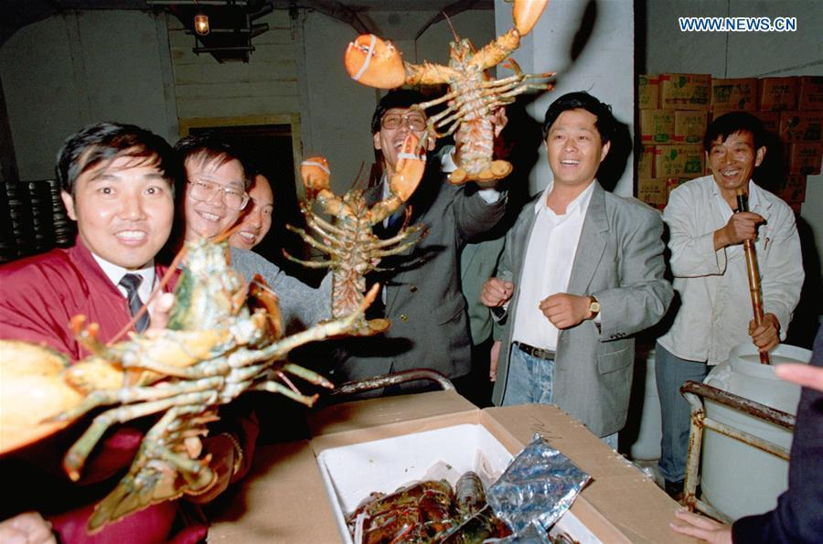 People show lobsters imported from Canada after they were flown in by a 20-hour journey to Shanghai, east China, Oct. 8, 1992. (Xinhua/Zhang Ming)