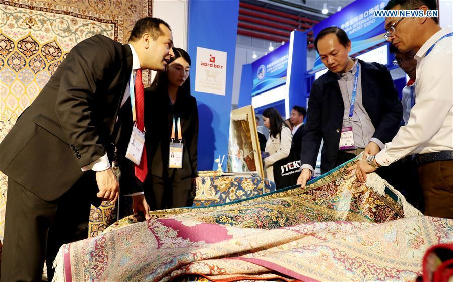 An Iranian exhibitor (L) introduces carpets at the First China International Import Expo in Shanghai, east China, Nov. 5, 2018. (Xinhua/Fang Zhe)