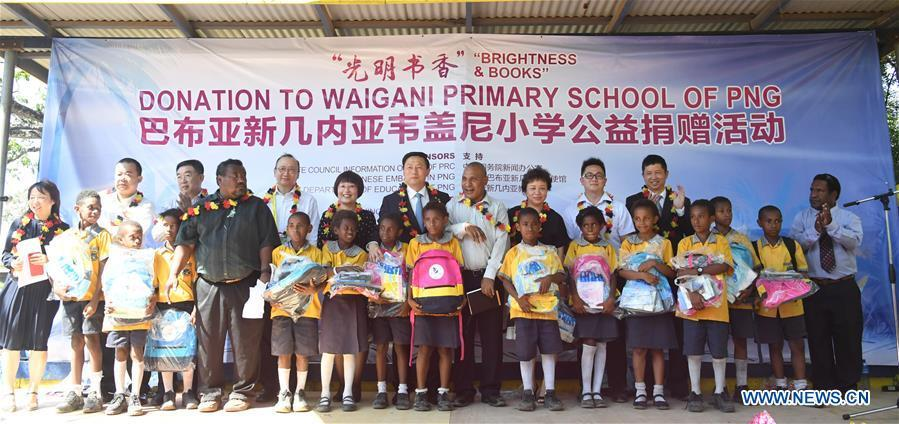 Guo Weimin (C), deputy director of the State Council Information Office of China, attends a donation ceremony to a local primary school in Port Moresby, Papua New Guinea, on Nov. 12, 2018. A series of cultural exchange activities were held here on Monday between China and Papua New Guinea (PNG) ahead of the Asia-Pacific Economic Cooperation (APEC) Leaders\' Meeting. (Xinhua/Lui Siu Wai)