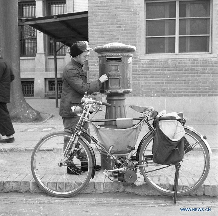 File photo taken on Feb. 19, 1959 shows a postman collecting mails from a mailbox in Beijing, capital of China. The postman used a modified bicycle equipped with engine to ride faster, a move made by local authority to accelerate the delivery of letters. More than four decades of sound economic growth from 1978, the starting year of the reform and opening-up policy, has fundamentally lifted life quality of 1.3 billion Chinese, who are now able to enjoy the \