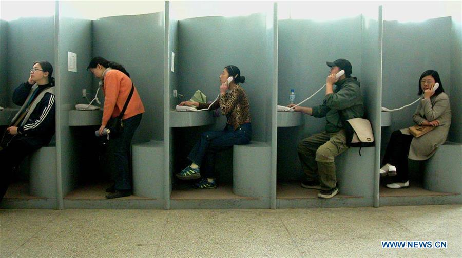 People make long-distance phone calls at a public booth in Yan\'an, northwest China\'s Shaanxi Province, April 23, 2002. More than four decades of sound economic growth from 1978, the starting year of the reform and opening-up policy, has fundamentally lifted life quality of 1.3 billion Chinese, who are now able to enjoy the \