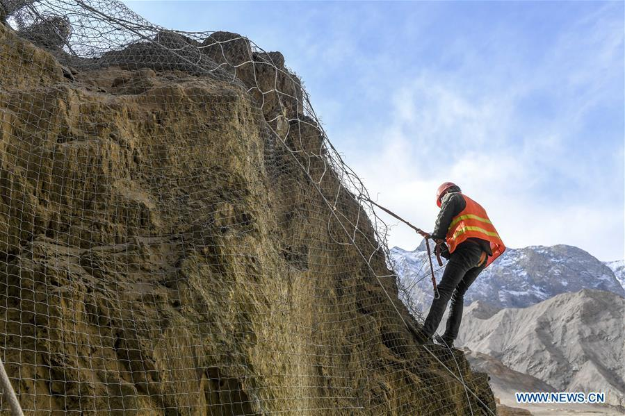 A construction worker installs protective nets on a cliff at a road section in the Tajik Autonomous County of Taxkorgan, northwest China\'s Xinjiang Uygur Autonomous Region, Nov. 12, 2018. The job of this team of construction workers is to install protective facilities on the cliff of risky road sections in the mountainous areas in Xinjiang, protecting pedestrians and vehicles from fallen stones. (Xinhua/Hu Huhu)