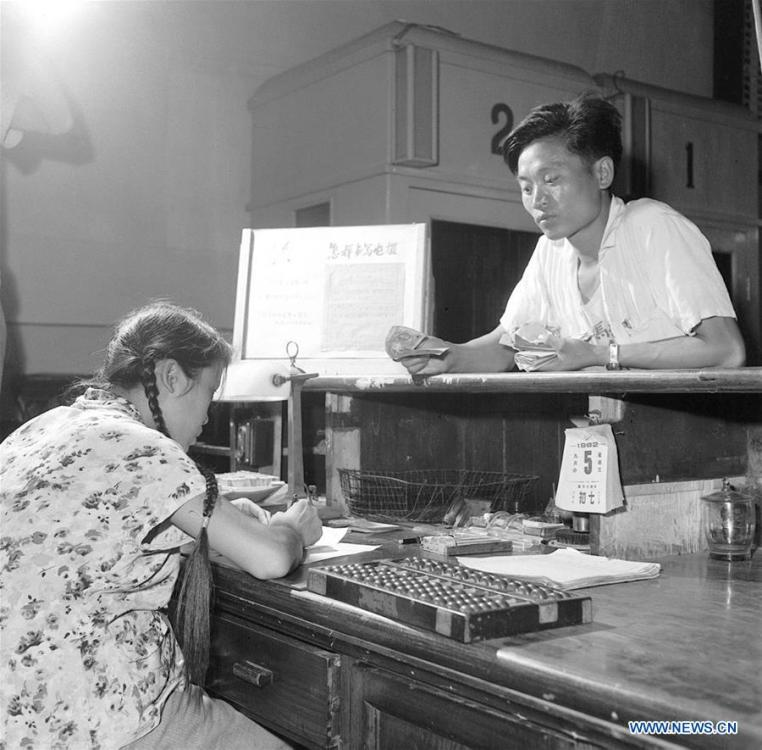 Photo taken on Aug. 30, 1962 shows telegraph operator Li Huiqing (L) helps a man send a telegram at Dongsi telecom bureau in Beijing, capital of China. More than four decades of sound economic growth from 1978, the starting year of the reform and opening-up policy, has fundamentally lifted life quality of 1.3 billion Chinese, who are now able to enjoy the \