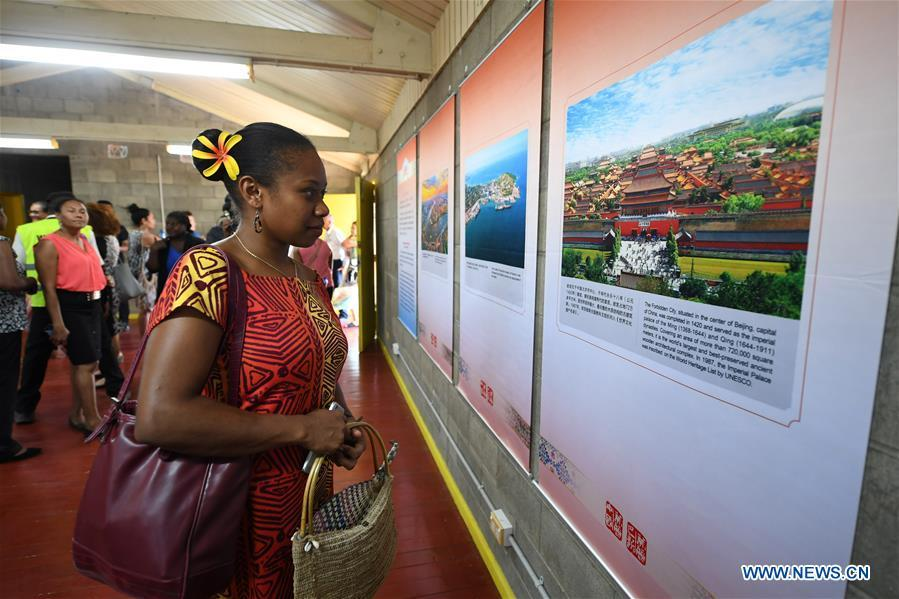 People visit a photo exhibition displaying 100 pictures on the two countries\' landscapes, cultures and society, in Port Moresby, Papua New Guinea, on Nov. 12, 2018. A series of cultural exchange activities were held here on Monday between China and Papua New Guinea (PNG) ahead of the Asia-Pacific Economic Cooperation (APEC) Leaders\' Meeting. (Xinhua/Lui Siu Wai)