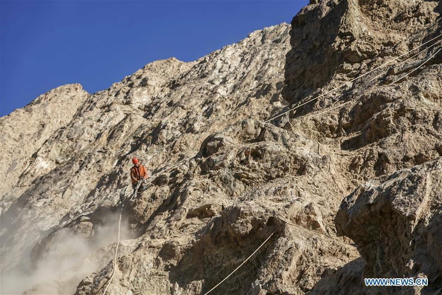 Construction worker Liu Quan works on a cliff at a road section in the Tajik Autonomous County of Taxkorgan, northwest China\'s Xinjiang Uygur Autonomous Region, Nov. 12, 2018. The job of this team of construction workers is to install protective facilities on the cliff of risky road sections in the mountainous areas in Xinjiang, protecting pedestrians and vehicles from fallen stones. (Xinhua/Hu Huhu)