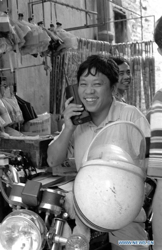 A merchant makes a call with a brick-size cellular phone in Guangzhou, southeast China\'s Guangdong Province, in January of 1994. More than four decades of sound economic growth from 1978, the starting year of the reform and opening-up policy, has fundamentally lifted life quality of 1.3 billion Chinese, who are now able to enjoy the \