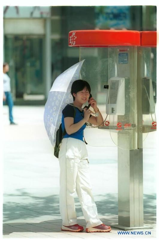 A woman makes a phone call at a phone booth in Beijing, capital of China, May 19, 2001. More than four decades of sound economic growth from 1978, the starting year of the reform and opening-up policy, has fundamentally lifted life quality of 1.3 billion Chinese, who are now able to enjoy the \