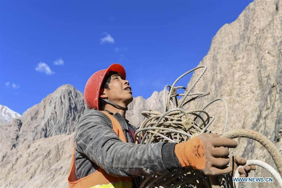 Construction worker Wang Huaguo transfers protective nets on a cliff at a road section in the Tajik Autonomous County of Taxkorgan, northwest China\'s Xinjiang Uygur Autonomous Region, Nov. 12, 2018. The job of this team of construction workers is to install protective facilities on the cliff of risky road sections in the mountainous areas in Xinjiang, protecting pedestrians and vehicles from fallen stones. (Xinhua/Hu Huhu)