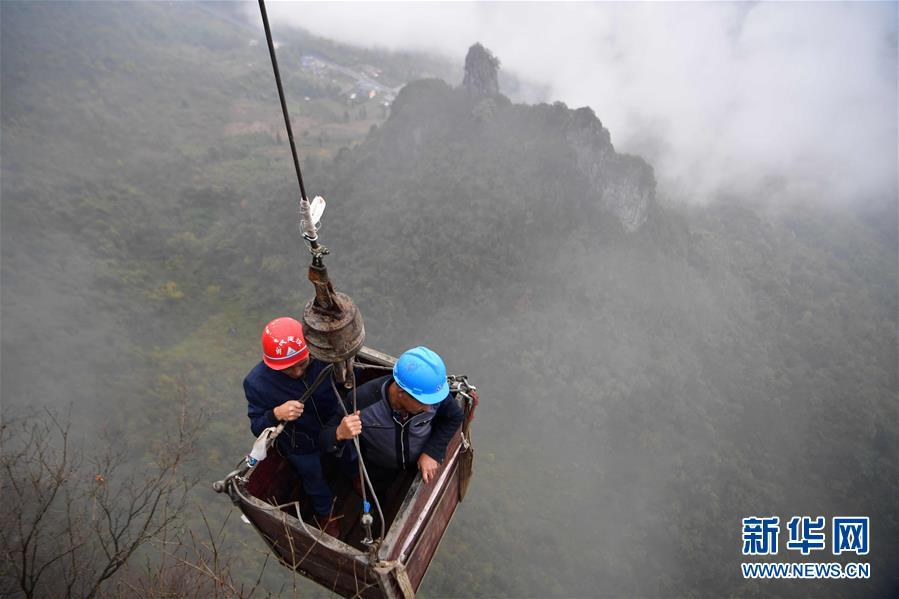Two water exploration team members are carried in an iron basket to the Tianbao cave in Tianfengping village, Enshi city, Central China\'s Hubei Province, to take water, Nov. 13, 2018. (Photo/Xinhua)