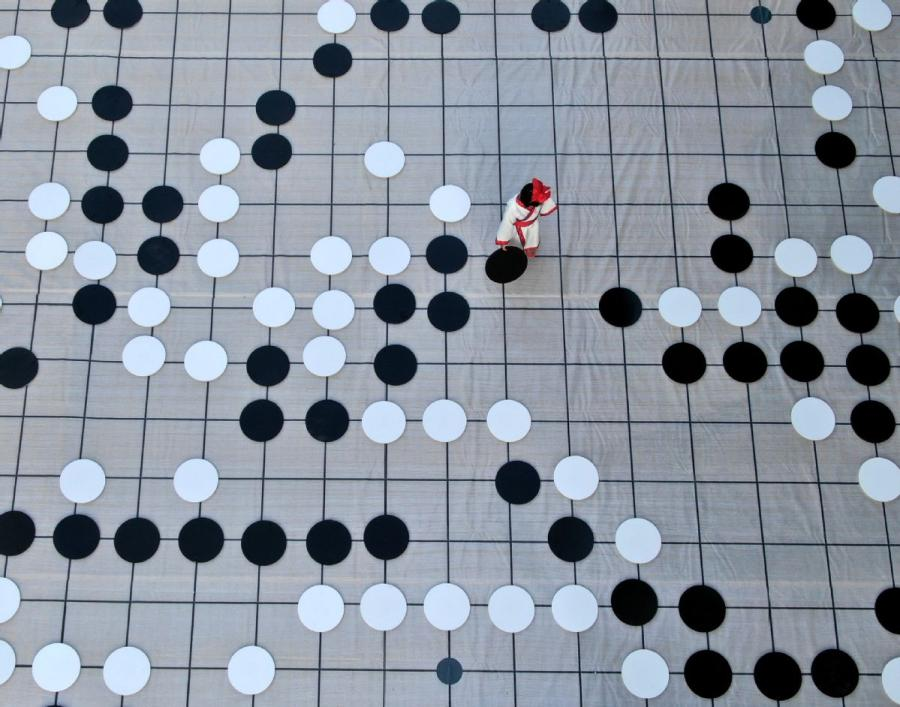 A player places a piece during a game of go on the sidelines of the finals of the third Chinese Weiqi Sage Title competition on Luoyang\'s Baiyun mountain in Henan Province, Nov. 12.  (Photo/Asianewsphoto)