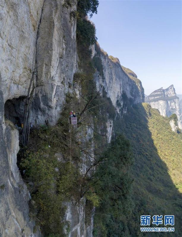 Water exploration team members reach the Tianbao cave in Tianfengping village by using an iron basket, Oct. 31, 2018.  (Photo/Xinhua)