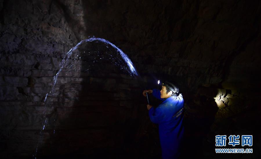 A water exploration team member uses pipes to draw water from the Tianbao cave in Tianfengping village, Enshi city, Central China\'s Hubei Province, Oct. 31, 2018.  (Photo/Xinhua)