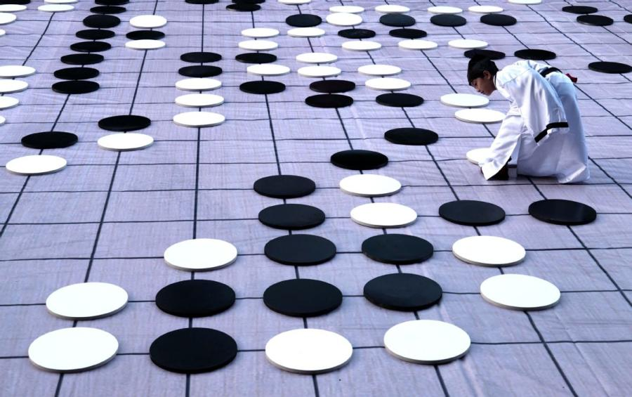 A player places a piece on Monday during a game of go on the sidelines of the finals of the third Chinese Weiqi Sage Title competition on Luoyang\'s Baiyun mountain in Henan Province. (Photo/Asianewsphoto)