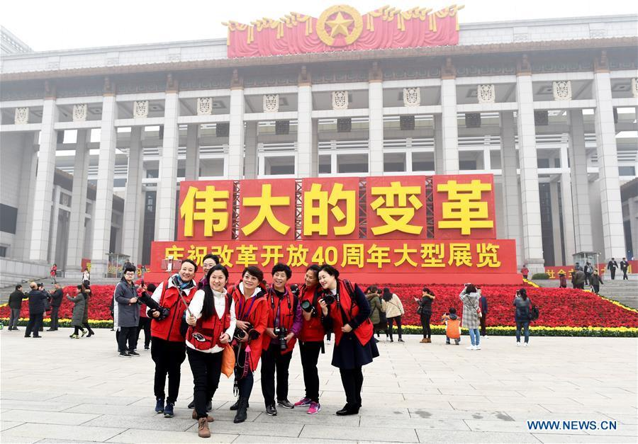 Visitors pose for photos in front of the National Museum of China, where a major exhibition to commemorate the 40th anniversary of China\'s reform and opening-up is held, in Beijing, capital of China, Nov. 14, 2018. (Xinhua/Luo Xiaoguang)
