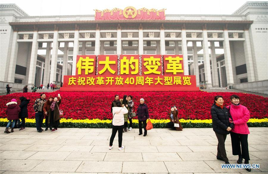 Visitors take photos in front of the National Museum of China, where a major exhibition to commemorate the 40th anniversary of China\'s reform and opening-up is held, in Beijing, capital of China, Nov. 14, 2018. The exhibition opened here on Tuesday. (Xinhua/Meng Dingbo)