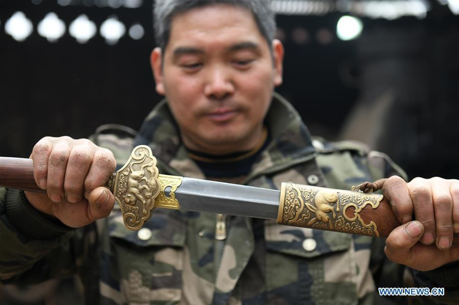 Li Zhujun shows a decorative sword made by him at his studio in Tiejiangzhuang Village of Xingtang County, Shijiazhuang, north China\'s Hebei Province, Nov. 14, 2018. For centuries, Tiejiangzhuang Village has been famed for its skillful blacksmiths and prosperous steel making industry. Li Zhujun is one of the village\'s top steel makers. Based on the skills inherited from his father, Li gained an expertise in the steel-making technique \