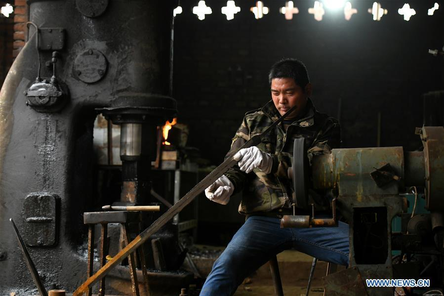 Li Zhujun makes a decorative sword at his studio in Tiejiangzhuang Village of Xingtang County, Shijiazhuang, north China\'s Hebei Province, Nov. 14, 2018. For centuries, Tiejiangzhuang Village has been famed for its skillful blacksmiths and prosperous steel making industry. Li Zhujun is one of the village\'s top steel makers. Based on the skills inherited from his father, Li gained an expertise in the steel-making technique \
