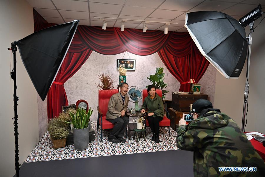 Two visitors pose for photos in a vintage image studio set at a major exhibition to commemorate the 40th anniversary of China\'s reform and opening-up at the National Museum of China in Beijing, capital of China, Nov. 15, 2018. Vintage objects are displayed at the exhibition which opened here on Tuesday to show visitors the history, accomplishments, and experience of China\'s reform and opening-up.(Xinhua/Li Xin)