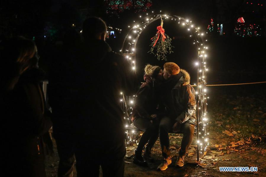 A couple pose for photos under a light decoration during the \